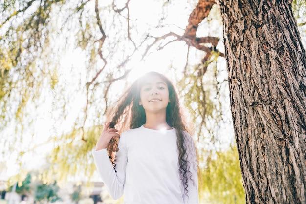 Faible angle de vue d'une jeune fille souriante, debout sous l'arbre au soleil Photo gratuit