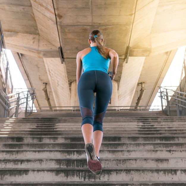 Faible angle de vue de jogger féminin en cours d'exécution sur l'escalier sous le pont Photo gratuit