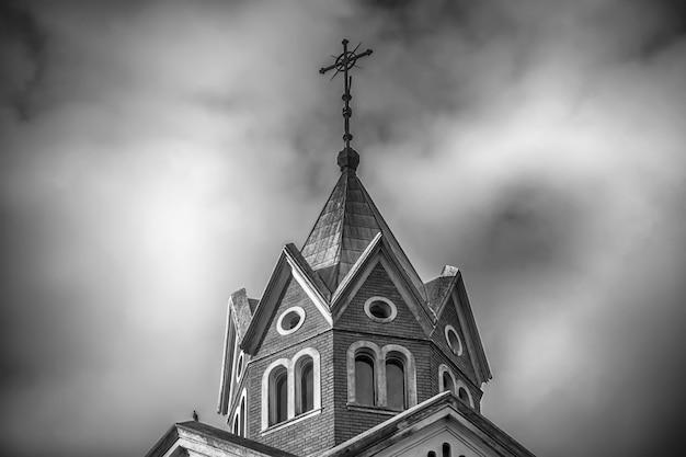 Faible Angle De Vue En Niveaux De Gris Du Haut D'une église Chrétienne Avec Ciel Nuageux Photo gratuit