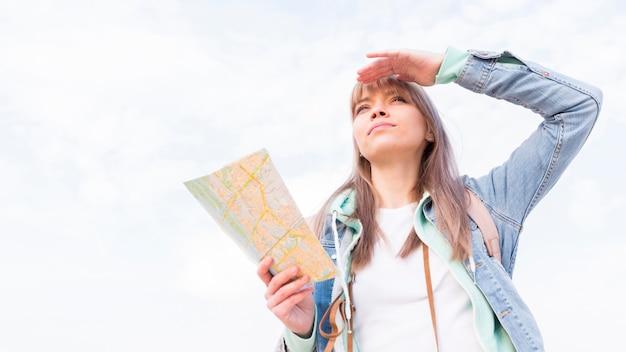 Faible angle de vue d'une voyageuse protégeant ses yeux contre le ciel Photo gratuit