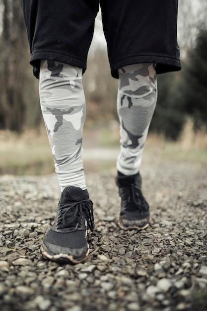 Faible section de chaussures de coureur masculin sur le chemin de gravier Photo gratuit