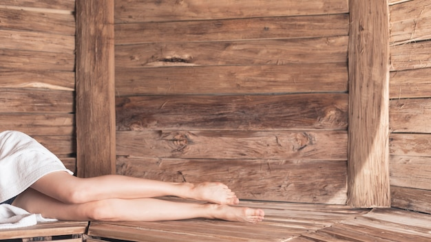 Faible section de femme allongée sur un banc en bois au sauna Photo gratuit