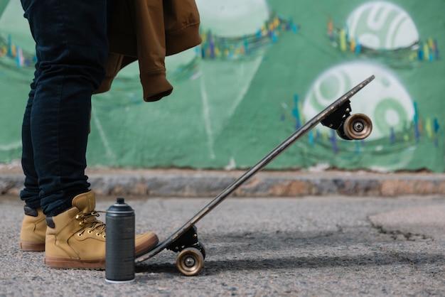 Faible section d'un homme avec skateboard et aérosol Photo gratuit