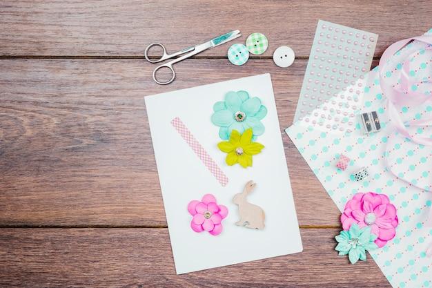 Faire une carte de voeux avec une fleur; boutons; ruban et perles sur table en bois Photo gratuit