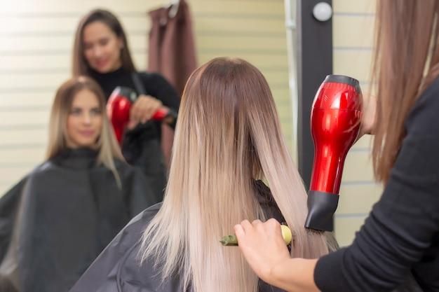 Faire Une Coiffure à L'aide D'un Sèche-cheveux. Femme Aux Cheveux Longs Blonds Dans Un Salon De Beauté. Salon De Coiffure. Photo Premium