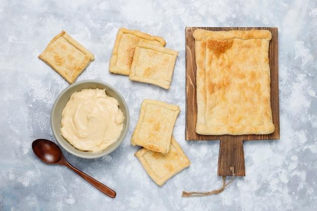 Faire une délicieuse pâte feuilletée avec de la crème épaisse sur le béton, vue de dessus Photo gratuit