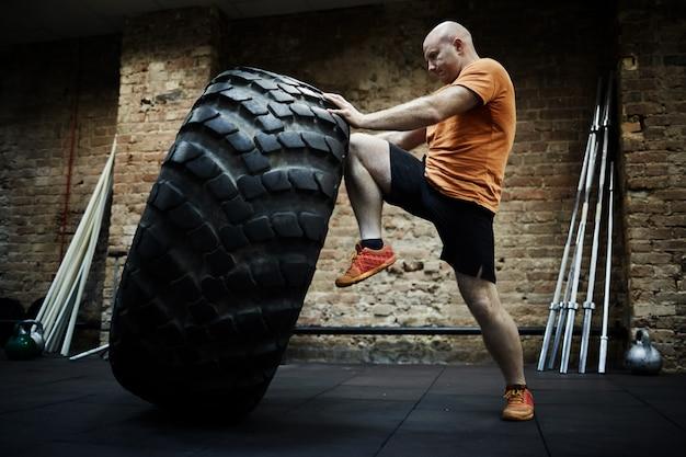 Faire de l'exercice avec un pneu énorme Photo gratuit