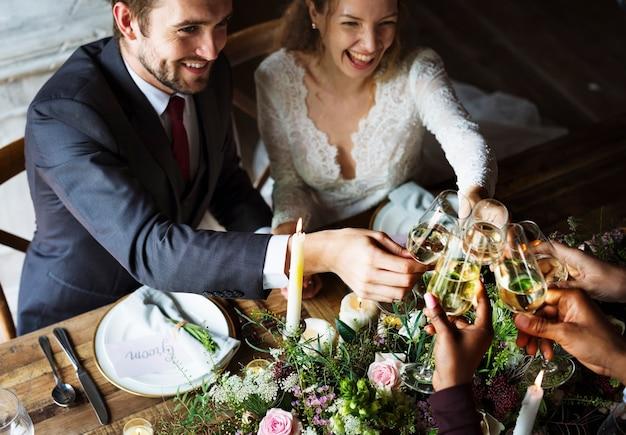 Faire griller les jeunes mariés avec des verres à vin lors d'une réception de mariage Photo Premium
