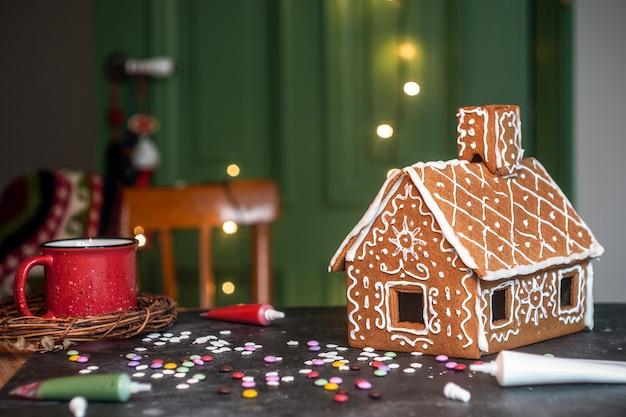 Faire De La Maison En Pain D'épice De Noël. Pâtisserie De Noël Traditionnelle Et Des Biscuits. Photo Premium