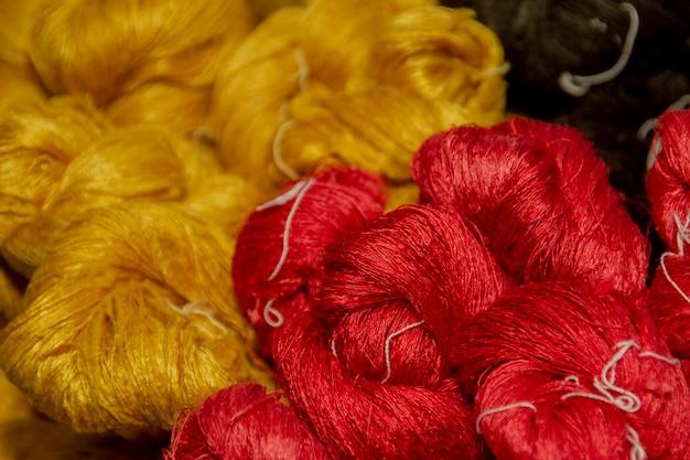 Faire de la soie avec des cocons de vers à soie blancs à la main. Photo Premium