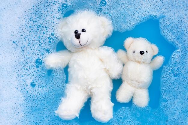 Faire tremper les ours en peluche dans une solution détergente de lessive avant Photo Premium