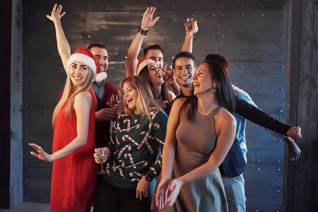 Faites La Fête Avec Des Amis. Ils Adorent Noël. Groupe De Jeunes Gais Portant Des Cierges Magiques Et Des Flûtes à Champagne Dansant Dans La Fête Du Nouvel An Et L'air Heureux. Concepts Sur Le Mode De Vie En Commun Photo Premium