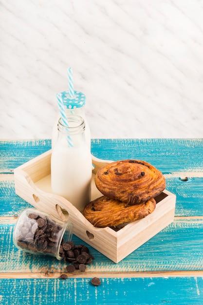 Faites tourbillonner les bouteilles de pâte et de lait dans le plateau près du pot de pépites de chocolat sur une surface en bois Photo gratuit