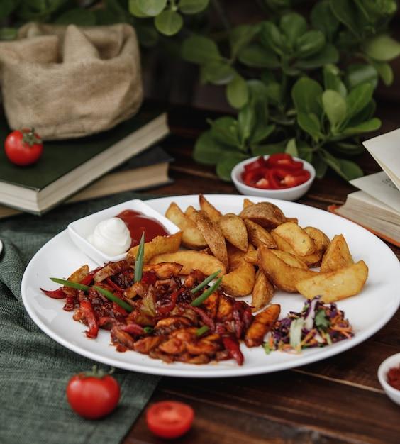 Fajitas de poulet mexicain avec pommes de terre rôties servies avec des sauces et une salade Photo gratuit