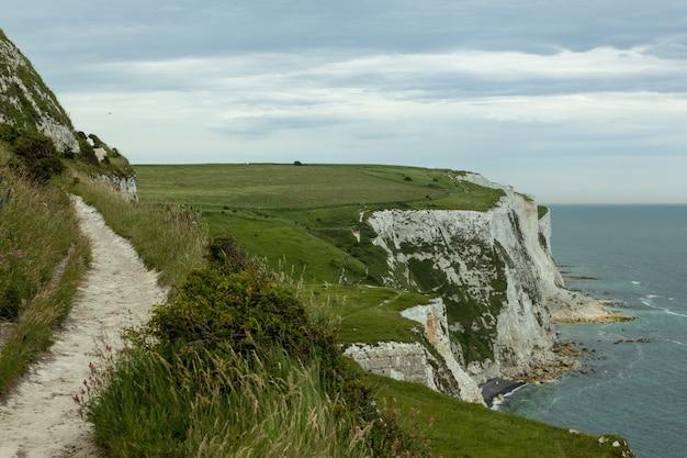 Falaises Blanches De Douvres Couvertes De Verdure Sous Un Ciel Nuageux Au Royaume-uni Photo gratuit