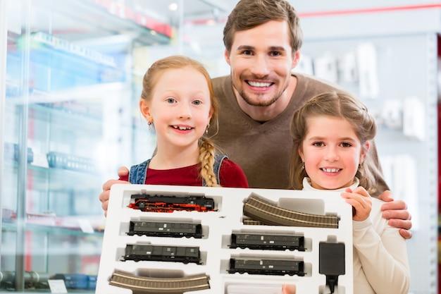 Famille achetant un chemin de fer modèle dans un magasin de jouets Photo Premium