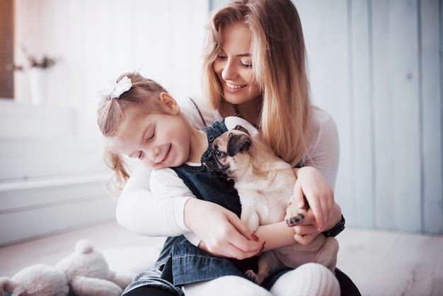 Famille Aimante Heureuse. Mère Et Sa Fille Enfant Fille Jouant Et étreignant Adorable Carlin Photo Premium