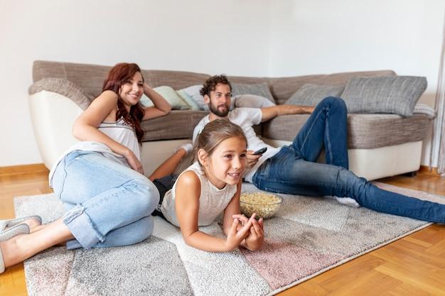 Famille allongée sur le sol en regardant la télévision Photo gratuit