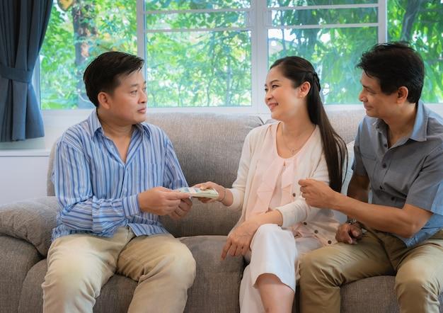 La famille d'amis a donné de l'argent pour aider ses amis en difficulté économique. Photo Premium