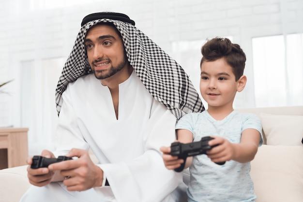 Une famille arabe traditionnelle joue à une console de jeux. Photo Premium
