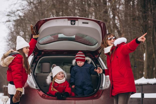 Famille assis à l'arrière de la voiture dehors en hiver Photo gratuit