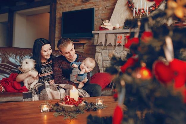 Famille Assis Sur Un Canapé Avec Arbre De Noël De Mise Au Point En Face Photo gratuit
