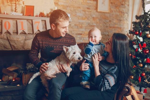 Famille Assis Sur Un Canapé Avec Un Chien à Noël Photo gratuit