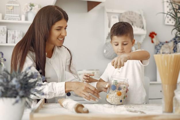 Famille assis dans une cuisine et faire cuire la pâte pour les cookies Photo gratuit
