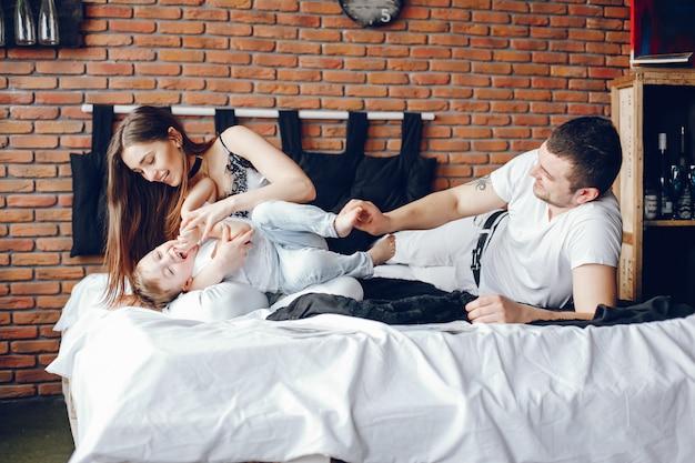 Famille assis dans un lit Photo gratuit