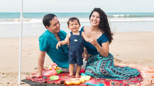 Famille assis ensemble sur la plage en été Photo gratuit