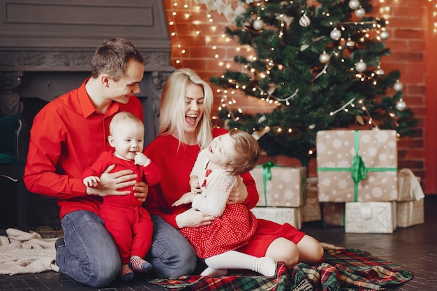 Famille assis à la maison près de sapin de noël Photo gratuit