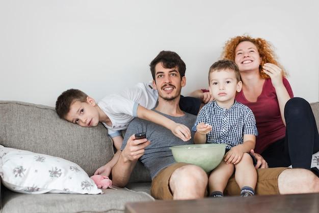 Famille assise sur un canapé devant la télévision à la maison Photo gratuit