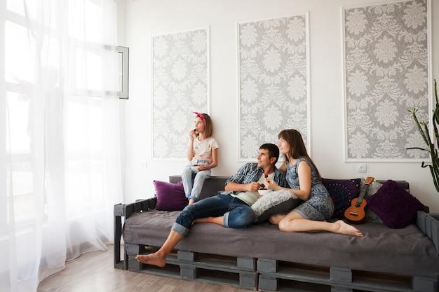 Famille Assise Sur Un Canapé Et Mangeant Des Fraises à La Maison Photo gratuit