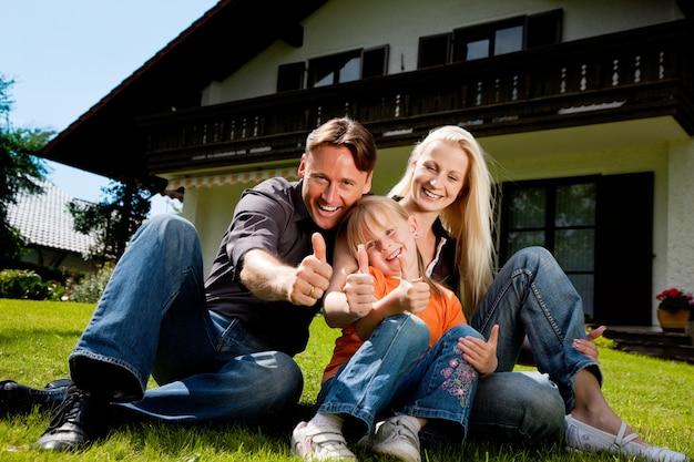 Famille assise devant leur maison Photo Premium