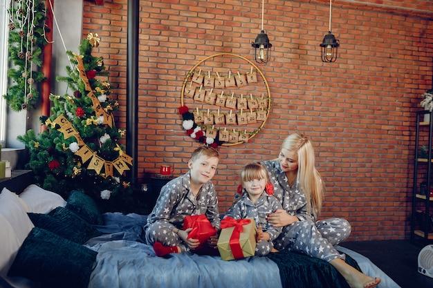 Famille assise sur un lit Photo gratuit