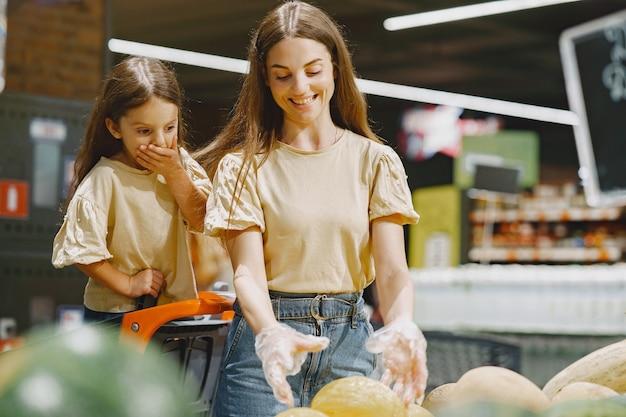 Famille Au Supermarché. Femme Dans Un T-shirt Marron. Les Gens Choisissent Les Légumes. Mère Avec Fille. Photo gratuit