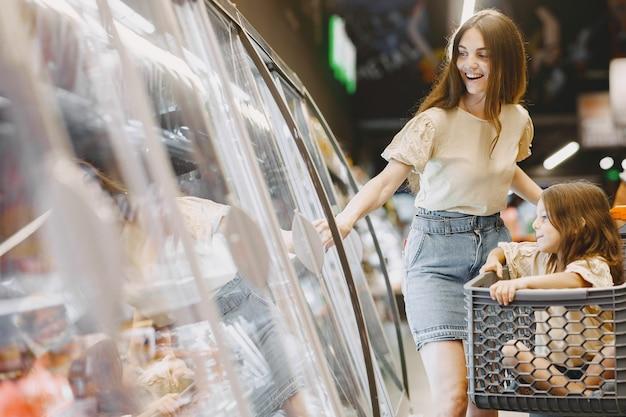 Famille Au Supermarché. Femme Dans Un T-shirt Marron. Les Gens Choisissent Les Produits. Mère Avec Fille. Photo gratuit