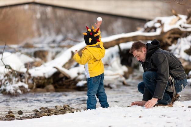 Famille ayant une promenade d'hiver à la rivière Photo Premium