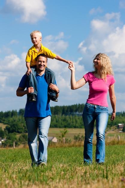 Famille ayant une promenade sur le pré Photo Premium