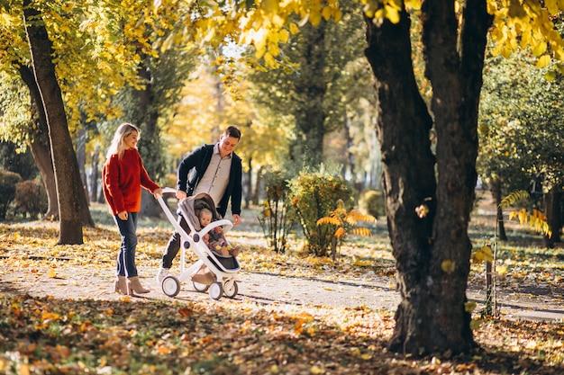 Famille avec bébé fille dans un landau à pied d'un parc en automne Photo gratuit