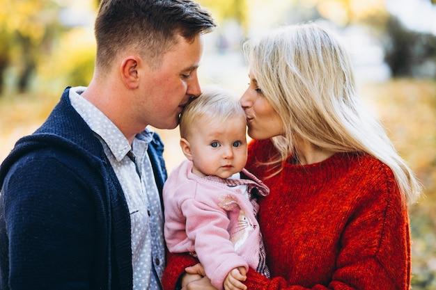 Famille avec bébé fille marchant dans un parc en automne Photo gratuit
