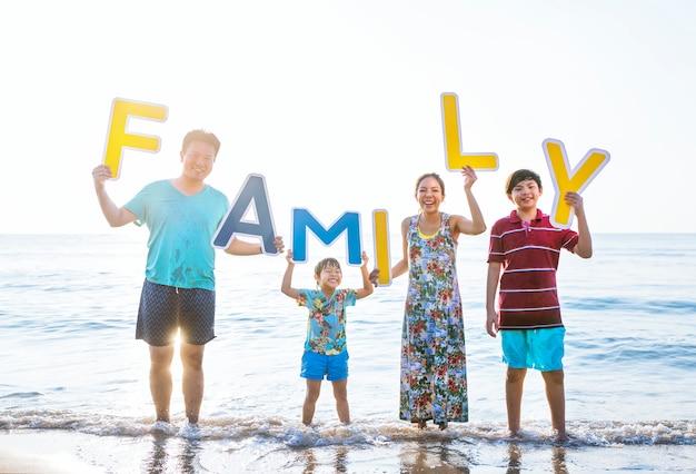 Famille brandissant des lettres à la plage Photo Premium