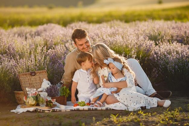 Famille Sur Champ De Lavande. Les Gens En Pique-nique. Mère Avec Enfants Mange Des Fruits. Photo gratuit