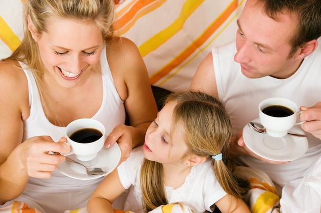 Famille et chat prenant son petit déjeuner au lit Photo Premium