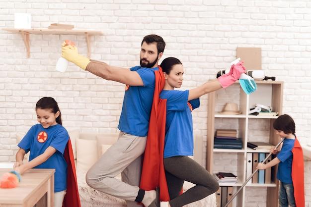 Famille en costume de super-héros pose sur l'appareil photo à la maison. Photo Premium