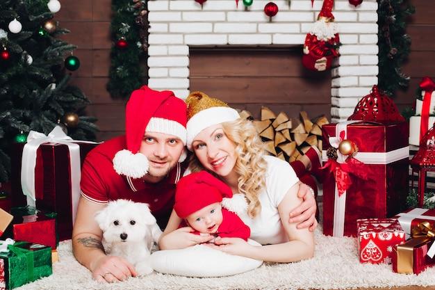 Famille, coucher plancher, près, cheminée, petit fils, chien, sourire, à, caméra Photo Premium