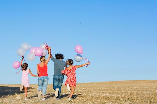 Famille en cours d'exécution dans le champ avec des ballons Photo gratuit