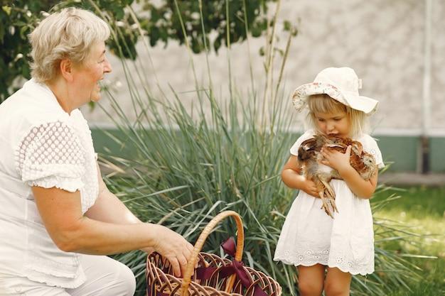 Famille Dans Un An. Petite-fille Avec Grand-mère. Les Gens Avec Peu De Poulet. Photo gratuit