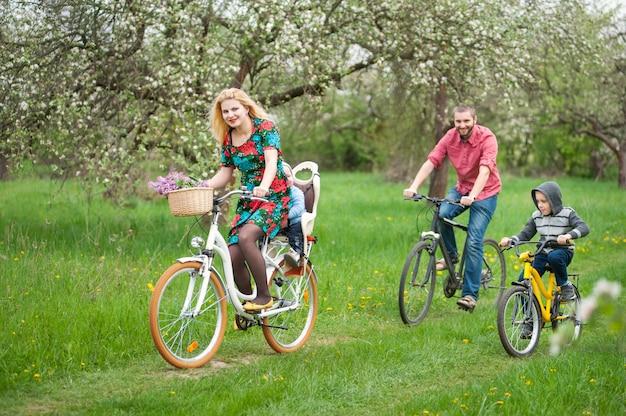 Famille avec deux enfants à vélo dans le jardin de printemps Photo Premium