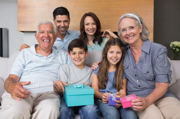 Famille élargie sur le canapé avec des boîtes-cadeaux dans le salon Photo Premium